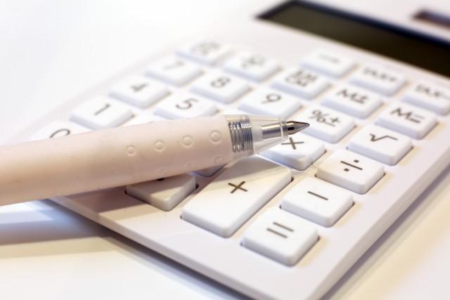 電卓とボールペンの画像